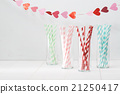 Colorful paper straws with a garland of hearts 21250417