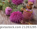 burdock oil in a bottle on a background of flowers 21263285
