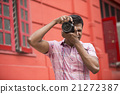 Asian Photographer shooting outside with digital camera. 21272387