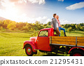 Senior couple sitting in back of red pickup truck 21295431