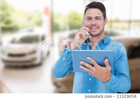 Composite image of handsome man holding digital tablet while tal 21329058