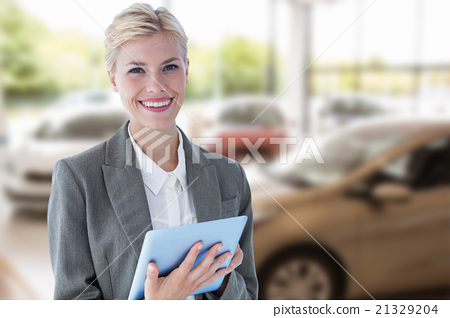 Composite image of smiling buisnesswoman using digital tablet 21329204
