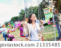 Mother and daughter at fun fair, chain swing ride 21335485