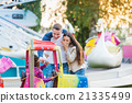 Parents at fun fair, waving their child taking 21335499