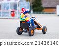Little kid boy having fun on toy race car outdoors 21436140