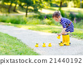 Little girl playing in forest and wearing boots 21440192