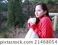 A warm drink and a girl indulging in thought in the winter forest 21468054