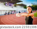 Young woman taking exercise on running track 21501306
