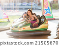 Mother and daughter in bumper car at fun fair 21505670