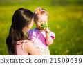 Little girl smelling field flowers 21509639