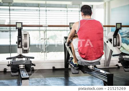 Muscular man on rowing machine 21525269