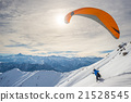 Paraglider launching from snowy slope 21528545