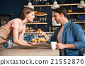 Nice waiter giving croissant to her client 21552876
