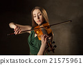 Beautiful young woman playing violin over black 21575961