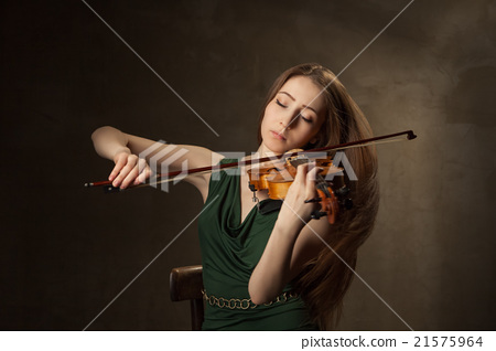 Beautiful young woman playing violin over black 21575964