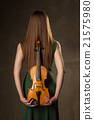 Beautiful young woman playing violin over black 21575980