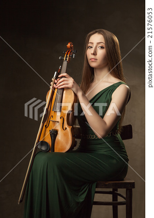Beautiful young woman playing violin over black 21576053