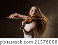 Beautiful young woman playing violin over black 21576098