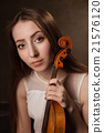 Beautiful young woman playing violin over black 21576120