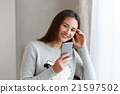 Youngsmiling woman chatting to her friends on the 21597502