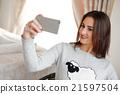 Portrait of a beautiful brunette taking a selfie 21597504