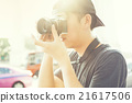 Portrait of young photographer shooting photo 21617506
