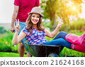 Couple with man giving woman ride in wheelbarrow 21624168