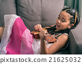 Happy smiling girl learning to play the Ukulele 21625032