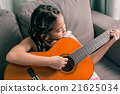 Happy smiling girl learning to play the a guitar 21625034