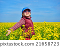 girl child in rapeseed field with bright yellow flowers, spring landscape 21658723