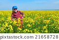 girl child in rapeseed field with bright yellow flowers, spring landscape 21658728