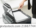 businesswoman pressing knob on copying machine 21667744