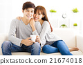sweet young couple sitting in sofa 21674018