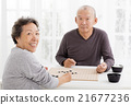 happy asian senior couple playing chess in living room 21677236