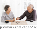 happy asian senior couple playing chess in living room 21677237