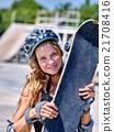 Girl holding a skateboard in hands. 21708416