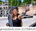 Girl holding a skateboard in hand. 21708420