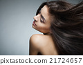 Attractive smiling woman with long hair on grey 21724657