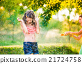 Boy splashing girl with water gun, sunny summer 21724758