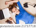 Young teenage girl lying on the floor with laptop 21737718