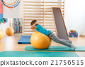 Young boy performs exercises in the gym. 21756515