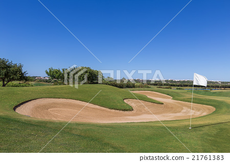 Sand trap on golf course with a white flag. 21761383