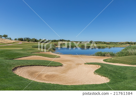 Sand trap on the golf course with a lake.  21761384