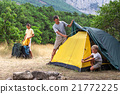 Family setting a tent in the meadow 21772225