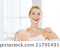 woman with toothbrush cleaning teeth at bathroom 21795491