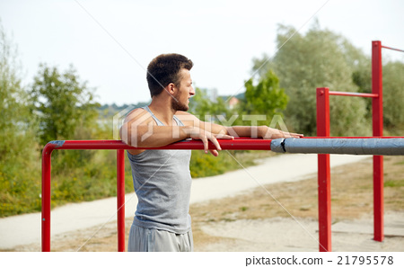 young man exercising on parallel bars outdoors 21795578