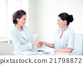 businesswomen shaking hands in office 21798872