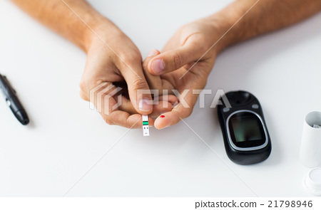 close up of man checking blood sugar by glucometer 21798946