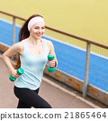 Young smiling woman jogging with dumbbells 21865464