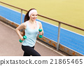 Young smiling woman jogging with dumbbells 21865465